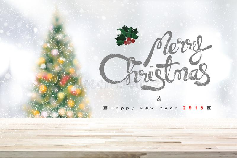 Merry Christmas and happy new year 2018 background with wood tab. Le top, blurred decorated pine tree and white snow falling - can be used for display or montage royalty free stock photos