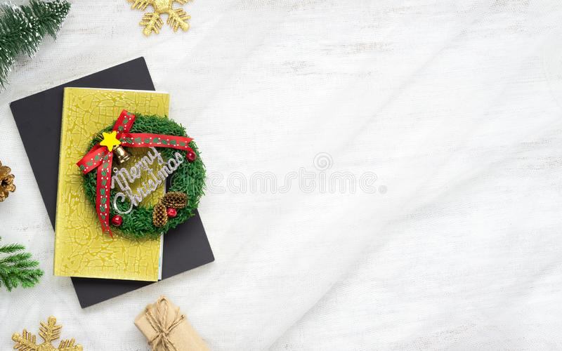Merry Christmas and Happy New Year background with xmas decorations, notebook and gift boxes on nest fabric on white wooden board. Flat lay top view with copy stock photos