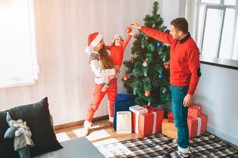 Merry Christmas and Happy New Year. Beautiful and bright picture of young family standing at Christmas tree. Man holds stock images