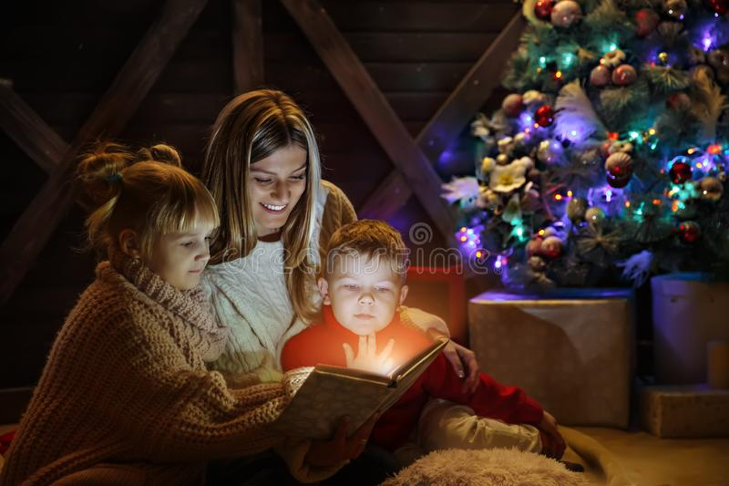 Merry Christmas and Happy New Year. Beautiful family in Xmas interior. Pretty young mother reading a book to her. Merry Christmas and Happy New Year. Beautiful stock photos