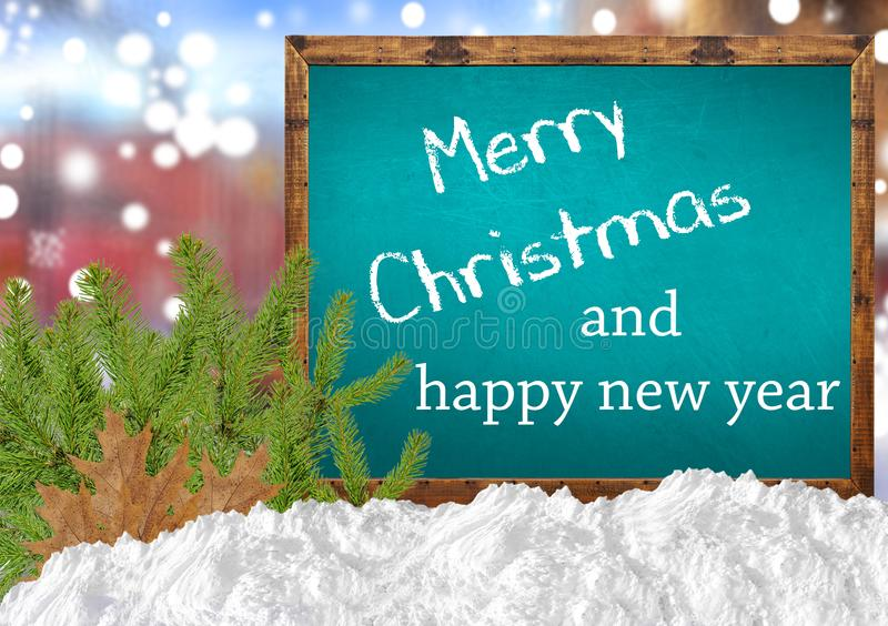Merry Christmas and happy new year on blue blackboard with blurr city pine and snow. Merry Christmas and happy new year on blue blackboard with blurr close royalty free stock image
