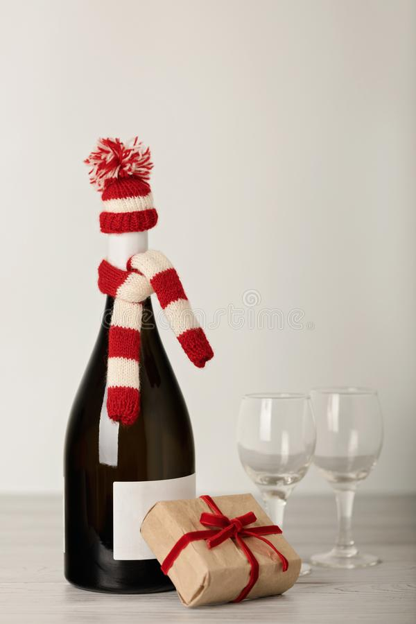 Merry Christmas and a Happy New Year! Bottle of wine in a knitted cap of Santa Claus. Selective focus royalty free stock image