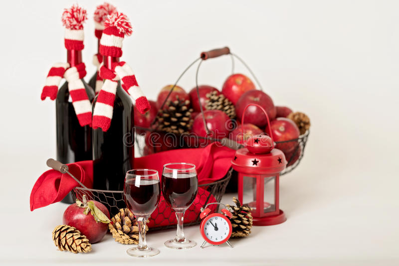 Merry Christmas and happy New year. Bottles of wine in a knitted. Santa hats, glasses and basket of apples stock photo
