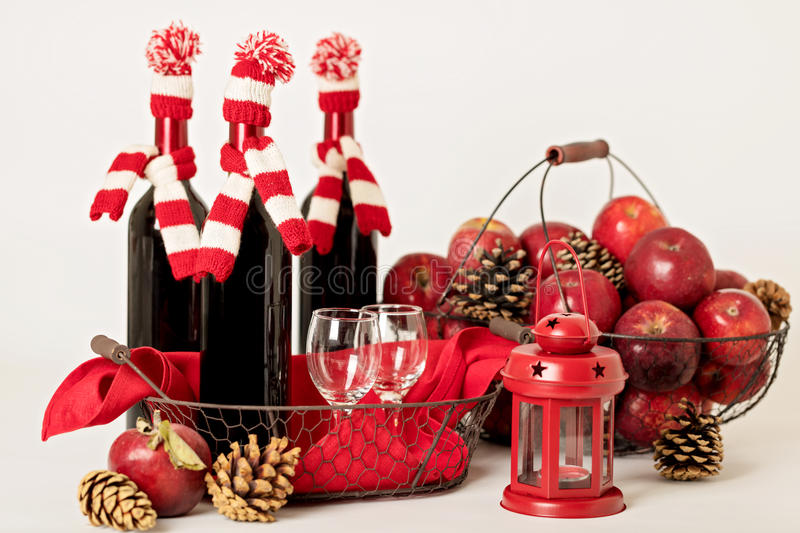 Merry Christmas and happy New year. Bottles of wine in a knitted. Santa hats, glasses and basket of apples stock photos