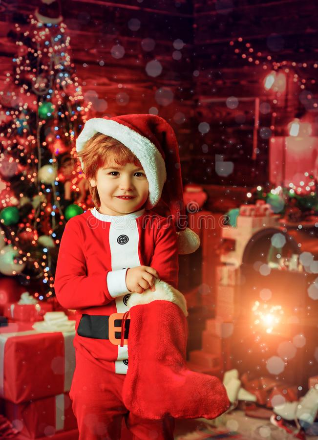 Merry Christmas and Happy New Year. Childhood moments. Kid boy santa hold christmas gift. Christmas stocking concept. Child cheerful face got gift in christmas royalty free stock photography