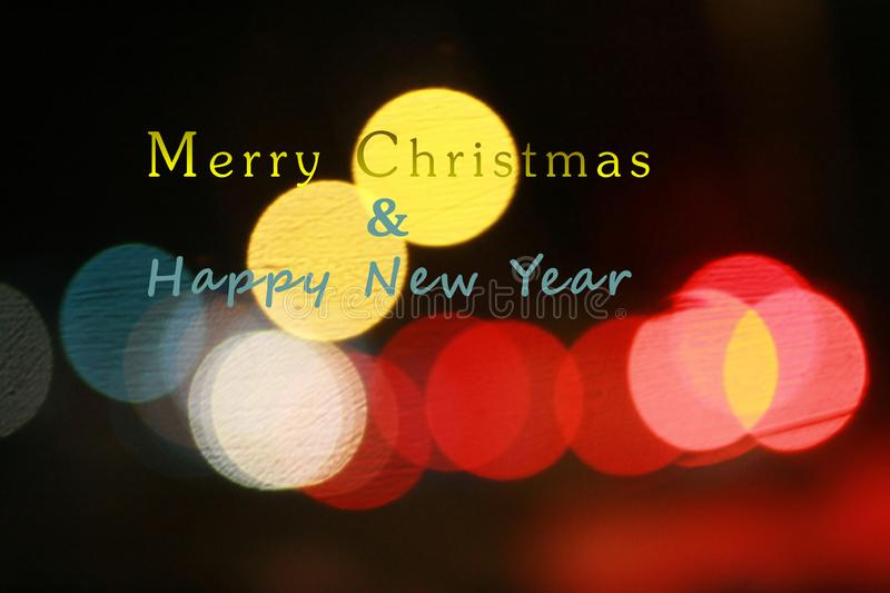 Merry Christmas and Happy New Year. With colorful bokeh light on black background. Christmas and New Year text design concept in stock images