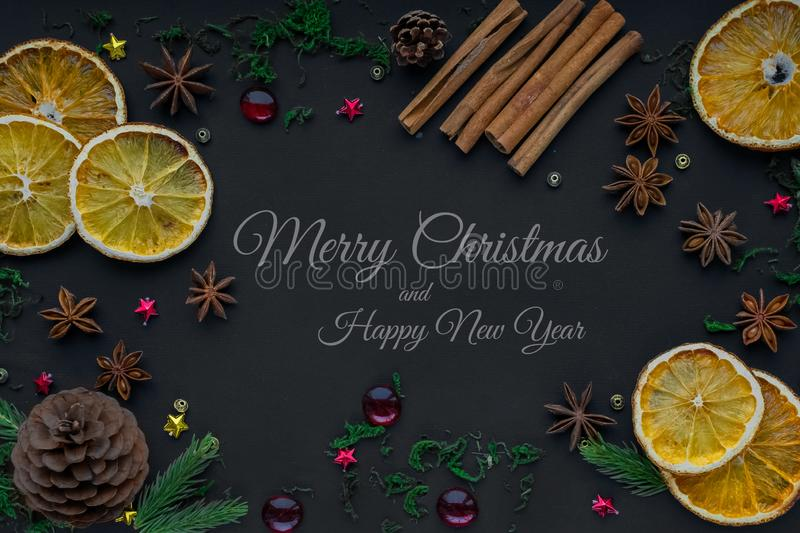 Merry Christmas and happy new year. composition on a black background of Christmas tree branches, cones, toys, cinnamon, dried. Oranges and anise. Greeting stock photos