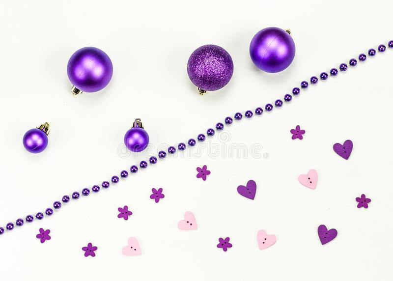 Merry Christmas and Happy New Year composition and decorations: Christmas toys, chaplet, pink purple hearts and flowers royalty free stock photo