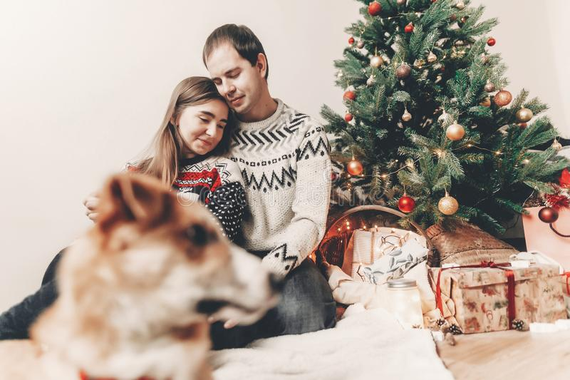 Merry christmas and happy new year concept. happy family in stylish sweaters hugging and cute dog at christmas tree with lights. And gifts. atmospheric festive stock photo