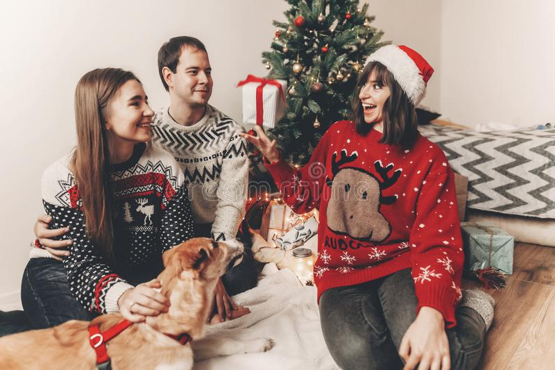 Merry christmas and happy new year concept. stylish hipster family in festive sweaters with cute dog tossing up gift at christmas. Tree lights. happy holidays stock photo