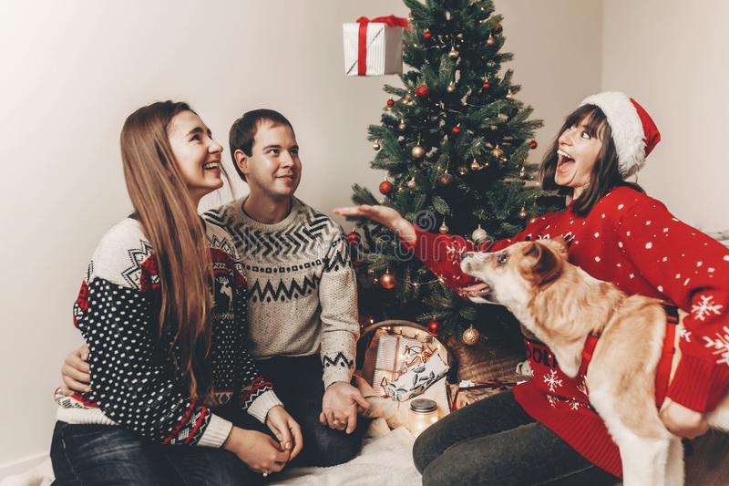 Merry christmas and happy new year concept. stylish hipster family in festive sweaters with cute dog tossing up gift at christmas. Tree lights. happy holidays royalty free stock image