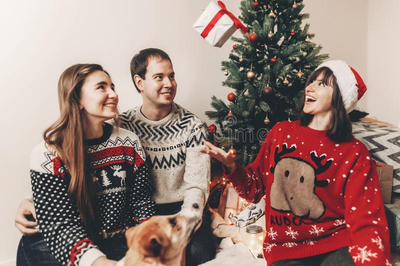 Merry christmas and happy new year concept. stylish hipster family in festive sweaters with cute dog tossing up gift at christmas. Tree lights. happy holidays royalty free stock images