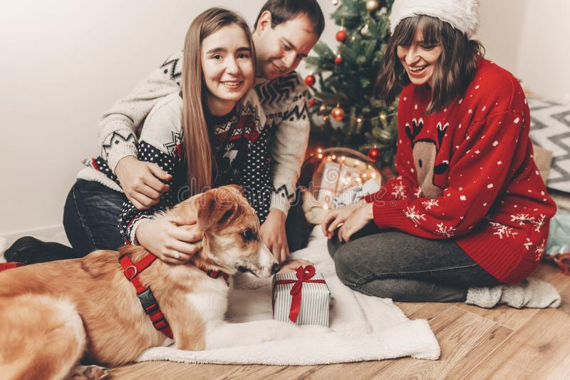 Merry christmas and happy new year concept. stylish hipster family in festive sweaters with a dog and gift at christmas tree. Lights. happy holidays. seasonal royalty free stock images