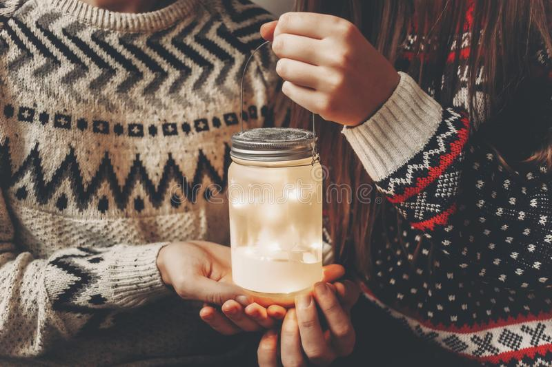 Merry christmas and happy new year concept. stylish hipster family in sweaters holding lantern light in festive room at christmas. Tree. happy holidays. cozy stock photography