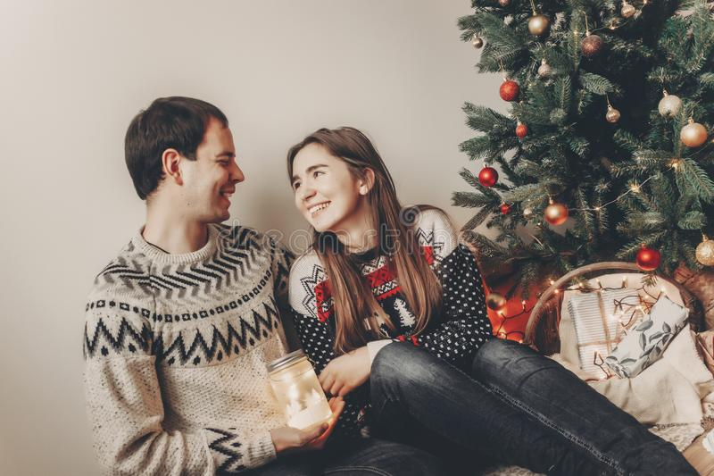Merry christmas and happy new year concept. stylish hipster family in sweaters holding lantern light in festive room at christmas. Tree. happy holidays. cozy royalty free stock photography