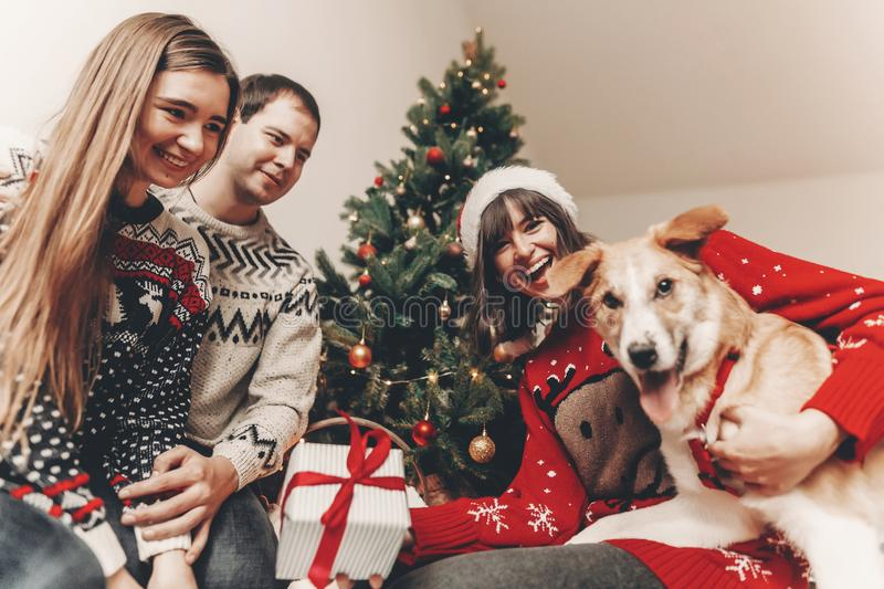 Merry christmas and happy new year concept. stylish hipster family in festive sweaters exchanging gifts at christmas tree lights. Happy holidays. funny royalty free stock image