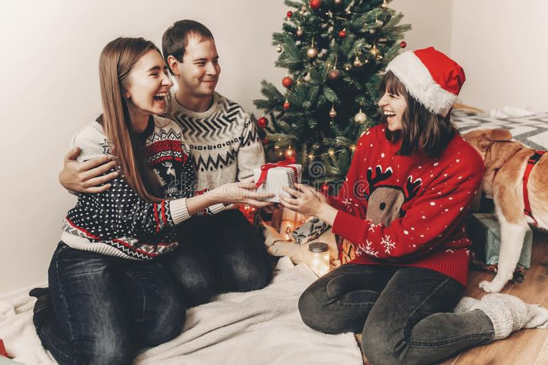 Merry christmas and happy new year concept. stylish hipster family in festive sweaters exchanging gifts at christmas tree lights. Happy holidays. funny royalty free stock photos