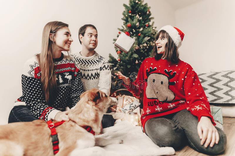 merry christmas and happy new year concept. stylish hipster family in festive sweaters with cute dog tossing up gift at christmas stock image