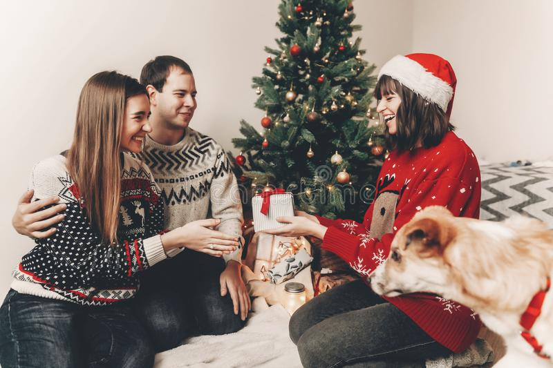 Merry christmas and happy new year concept. stylish hipster family in festive sweaters exchanging gifts at christmas tree lights. Happy holidays. funny stock photography