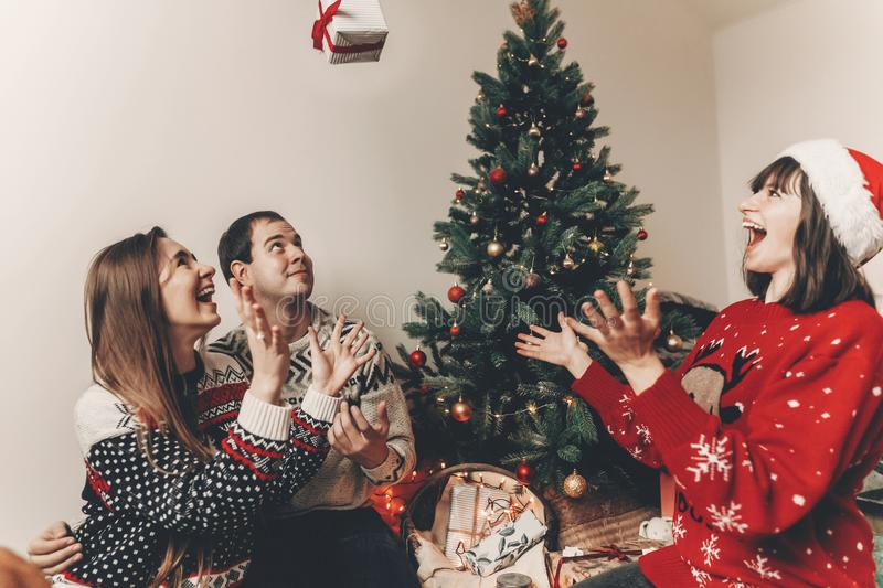 Merry christmas and happy new year concept. stylish hipster family in festive sweaters tossing up gifts at christmas tree lights. Happy holidays. funny stock image