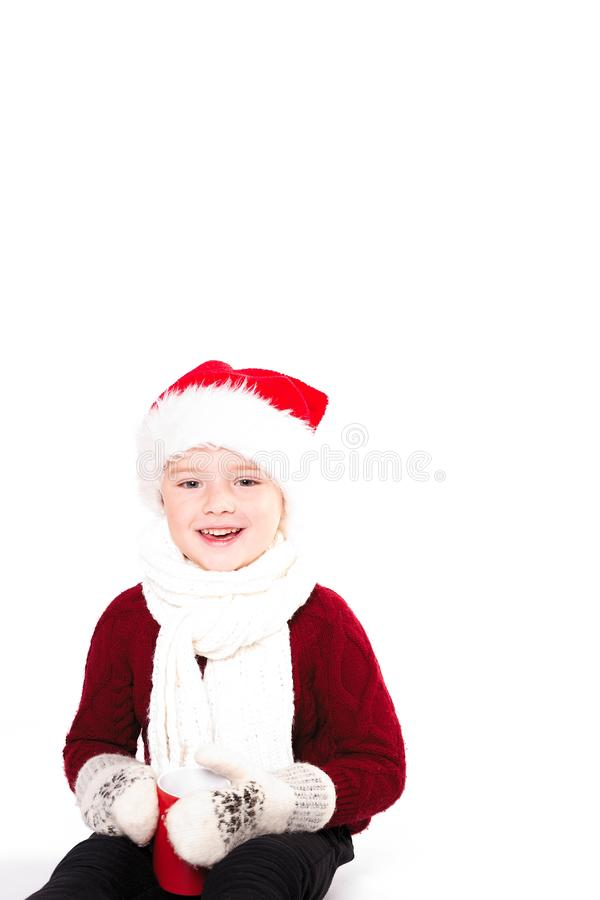 Merry Christmas and happy New year! Cute happy little boy holding red cup. Kid enjoy holiday santa hat. Portrait kid on light stock photo