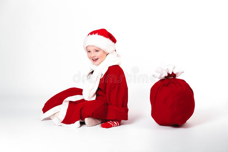 Merry Christmas and happy New year! Cute happy little boy sit wi. Th gift bag. Kid enjoy holiday in santa claus coat on light background. Happy Child with place royalty free stock photography