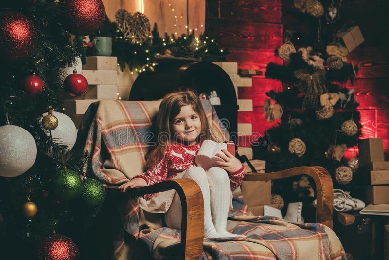 Merry christmas and happy new year. Cute little child girl play near christmas tree. Kid enjoy winter holiday at home royalty free stock photography