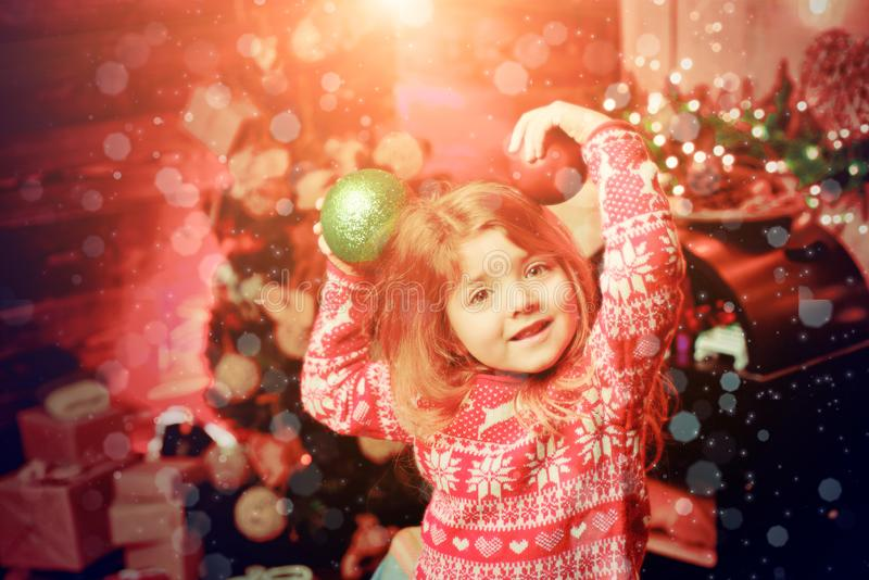 Merry christmas and happy new year. Cute little child girl play ornaments balls christmas tree. Kid enjoy winter holiday. At home. Home filled joy. Cozy stock photo
