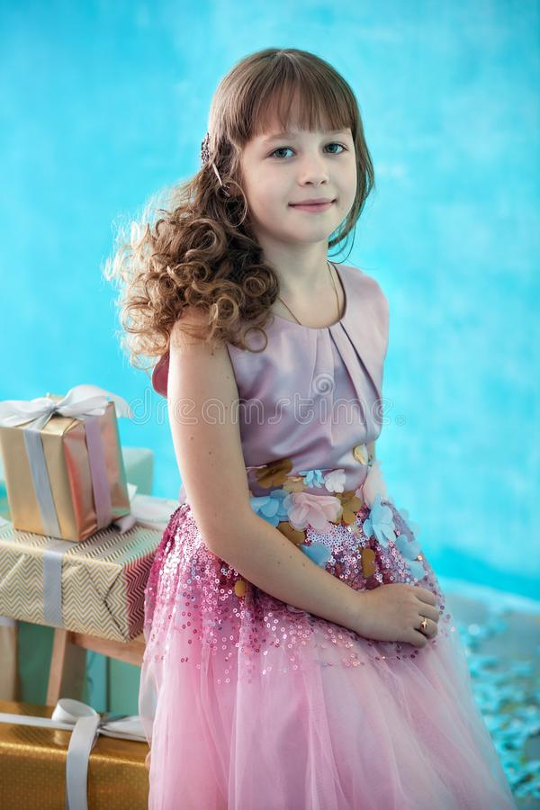 Merry Christmas and Happy New Year 2020! Cute little girl stands on the background of huge gifts. Birthday gift.  Happy child rece. Ives christmas presents stock photography
