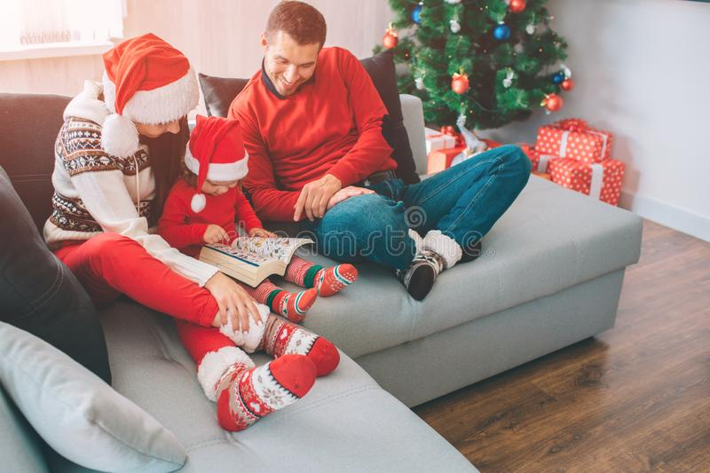 Merry Christmas and Happy New Year. Family sitting together on sofa. Small girl is in between her parents. She holds and. Looks at book with pictures. Man looks stock photography