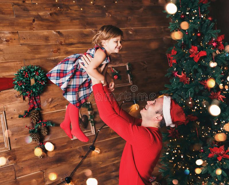 Merry Christmas and Happy New Year! Father and daughter smiling in living room decorated by christmas tree and xmas gift boxes stock photo
