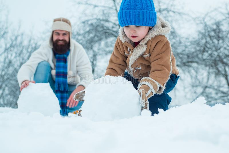Merry Christmas and Happy New Year. Happy father and son making snowman in the snow. Handmade funny snow man. royalty free stock photos