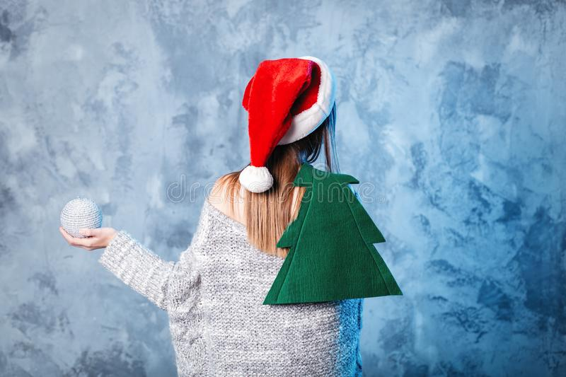 Merry Christmas and happy new year! Female hold christmas tree. Close portrait on gray background. Girl in santa hat and sweater. Back to camera stock image