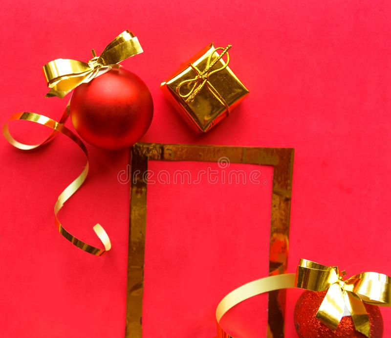 Merry Christmas and Happy New Year. Flat lay photo with golden mockup photo frame and Christmas decorations on bright red backgrou royalty free stock photography