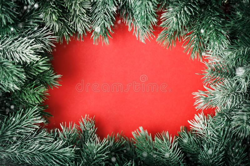 Merry Christmas and happy New year. A frame of fir-tree branches on a red background. Selective focus. Christmas royalty free stock images