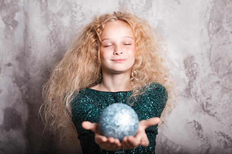 Merry Christmas and happy new year! happy girl with big ball toy in hands looks very pleased with closed eyes. Close portrait. Merry Christmas and happy new year royalty free stock image