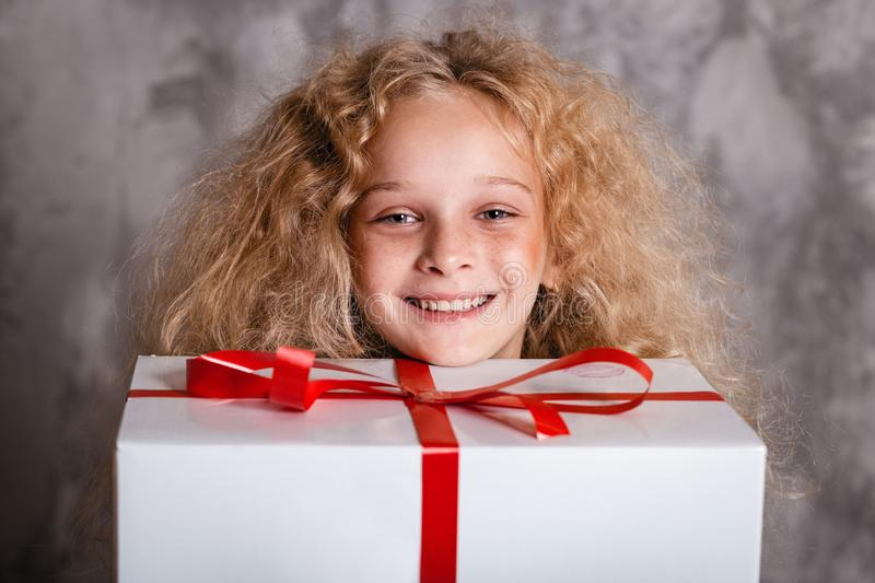 Merry Christmas and happy new year! happy girl with big present in hands looking in camera and smiling. Close portrait. Merry Christmas and happy new year! happy royalty free stock images