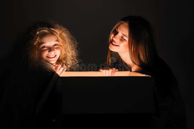 Merry Christmas and happy new year! happy girl near big present open it, and light from it blessing on her. Miracle in dark. Holiday time. Sisters looking in royalty free stock photo
