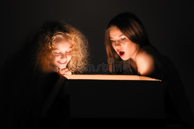 Merry Christmas and happy new year! happy girl near big present open it, and light from it blessing on her. Miracle in dark. Holiday time. Sisters looking in stock image