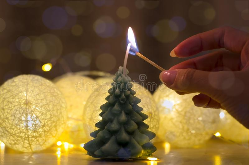 Merry Christmas and happy new year, greeting card. Beautiful decoration for the holidays. Hand of a girl who lights a candle. Merry Christmas and happy new year stock photography