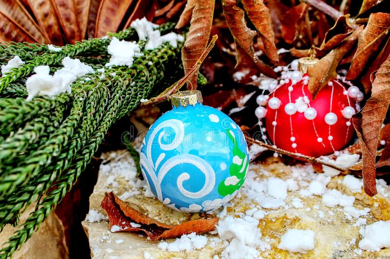 Merry Christmas and Happy New Year greeting card. Christmas balls. On natural stone, snow and trees stock images