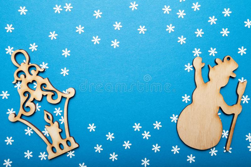 Merry Christmas and Happy New Year greeting card with copy space. Snowman and lantern on a blue background royalty free stock photography
