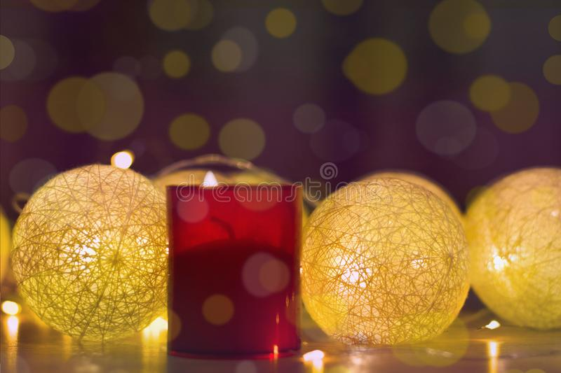 Merry Christmas and happy new year, greeting card. Decorative red background with a candle and golden bokeh garlands. Decorations with Cotton Ball Lights and a stock images