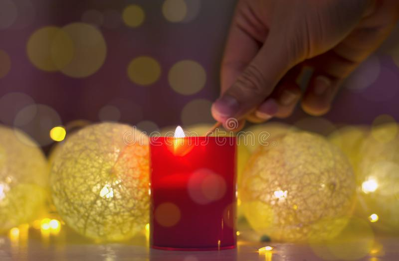 Merry Christmas and happy new year, greeting card. Hand that lights a candle.Beautiful decoration for the holidays. Hand that. Merry Christmas and happy new year stock photos