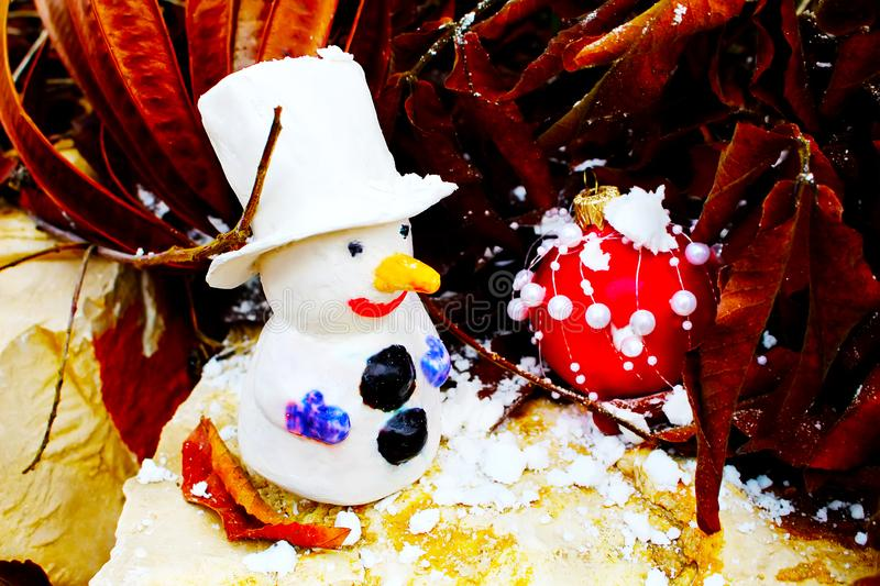 Merry Christmas or Happy New Year greeting card. Snowman and Red Christmas ball. On natural stone, snow and trees stock photos