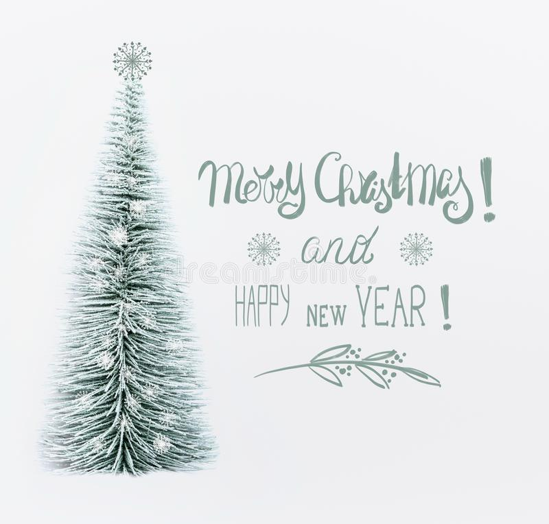 Merry Christmas and Happy New Year greeting card with text lettering and decorative artificial Christmas tree. With painted snowflakes on white background stock image
