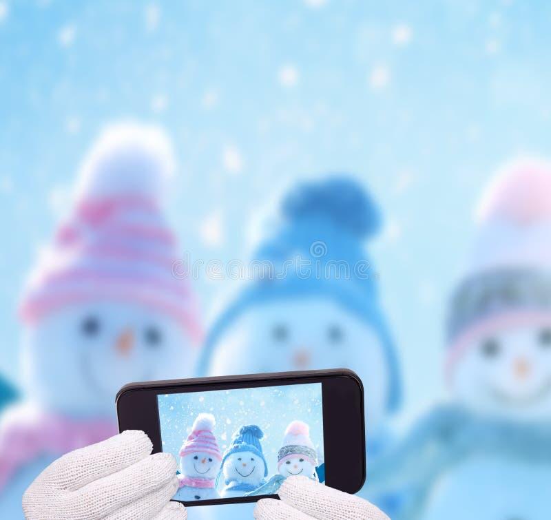 Three happy snowmen making selfie on smartphone. royalty free stock image