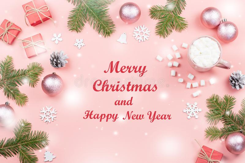 Merry Christmas and Happy New Year greeting card. Christmas tree and decorations on pink, top view royalty free stock image
