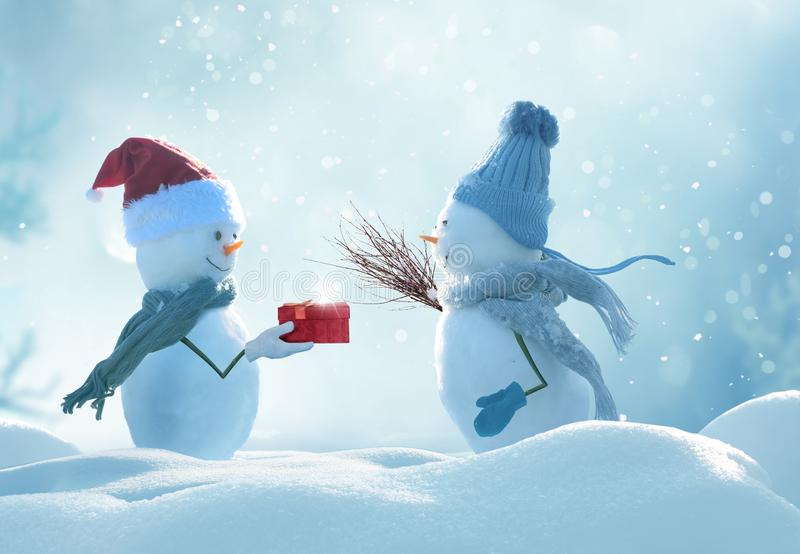 Two cheerful snowmen standing in winter christmas landscape. stock photos