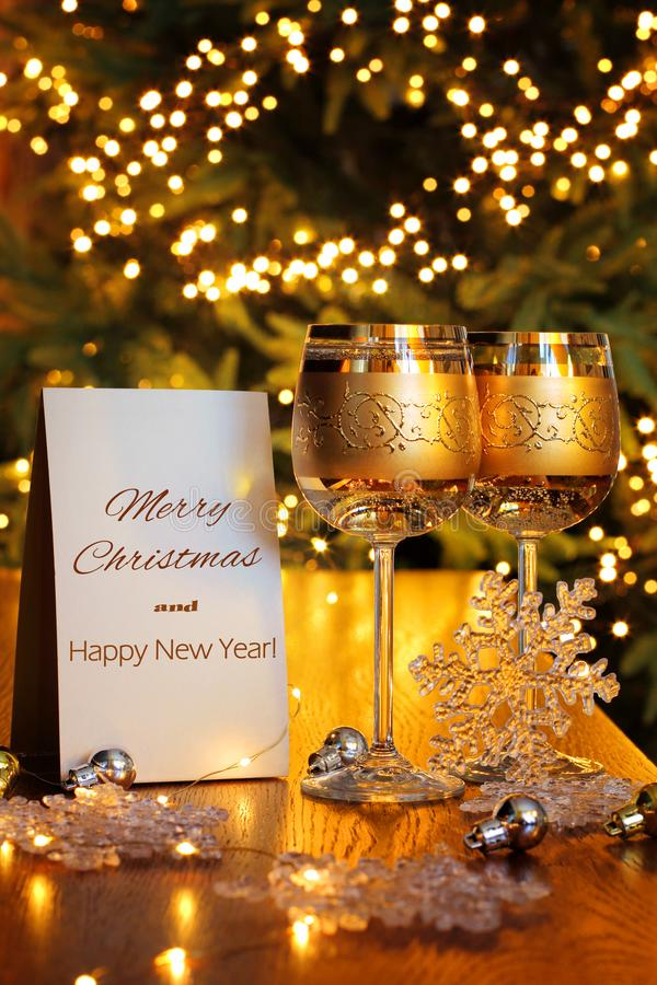 Merry Christmas and Happy New Year Greeting Card. Two wine glasses with an alcoholic drink on a blurred background of Christmas lights stock photo